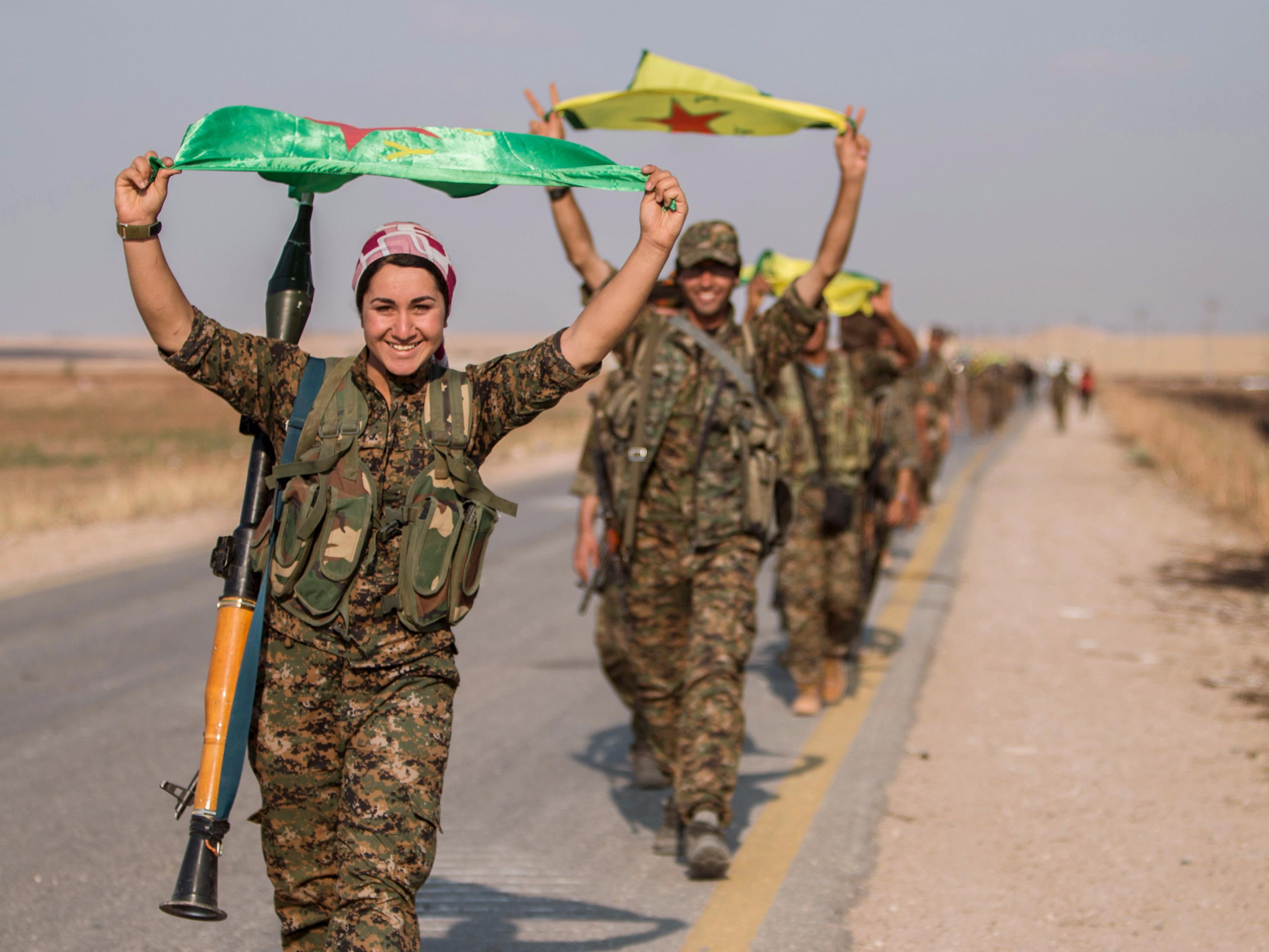 Syrian Kurdish militia fighters carry their flags in Tal Abyad on Monday after recapturing the town from Islamic State. Photo: Reuters